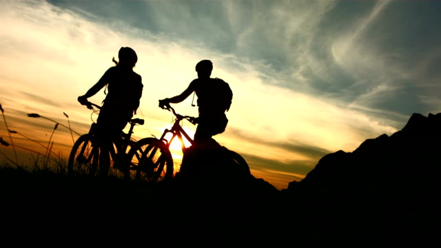 hd super slow-mo: mtb cyclists giving high-five - back lit stock videos & royalty-free footage
