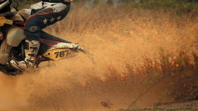 super slow-mo: mx rider riding through mud - motocross stock videos & royalty-free footage