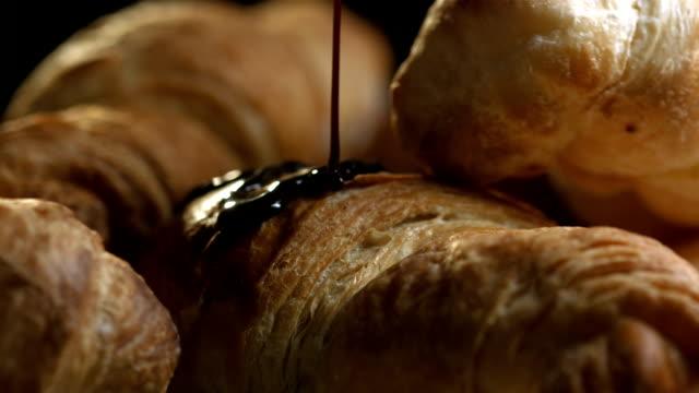 vídeos y material grabado en eventos de stock de hd super cámara lenta: el vertido de un jarabe de chocolate medialunas - dulces