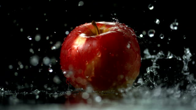 stockvideo's en b-roll-footage met hd super slow-mo: pouring water over an apple - sappig