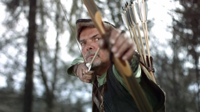 hd super slow-mo: robin hood shooting an arrow - longbow stock videos and b-roll footage