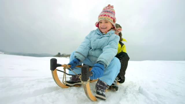 stockvideo's en b-roll-footage met hd super slow-mo: siblings sledging down the hill - vrijetijdsbesteding