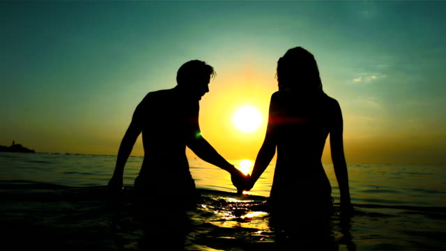 hd super slow-mo: silhouette of couple in the sea - desire stock videos & royalty-free footage