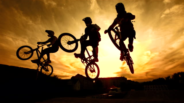 hd super slow-mo: silhouette of stunt bmx riders - stunt stock videos & royalty-free footage