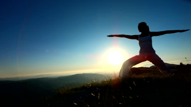 hd super slow-mo: silhouette practicing yoga on the ridge - early morning exercise stock videos & royalty-free footage