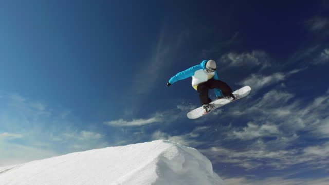 super slow-mo: snowboarder jumping over snow hill - acrobazia video stock e b–roll