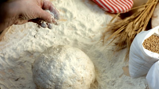 stockvideo's en b-roll-footage met hd super slow-mo: sprinkling flour on bread dough - strooisels