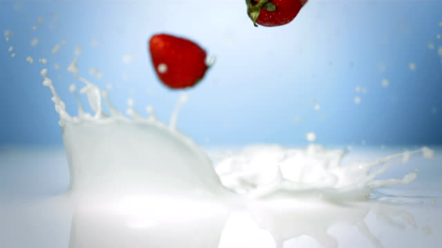 stockvideo's en b-roll-footage met hd super slow-mo: strawberries splashing into cream - melk
