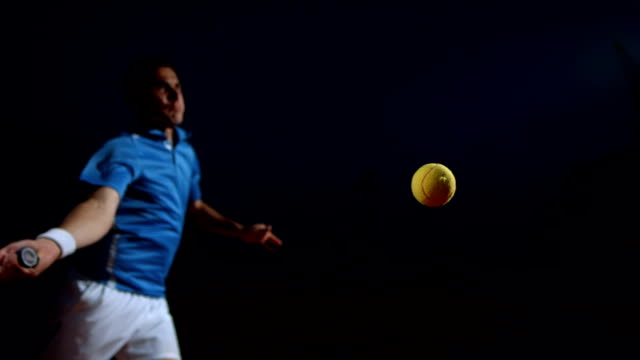 hd super slow-mo: tennis player in action at night - sportsperson stock videos & royalty-free footage