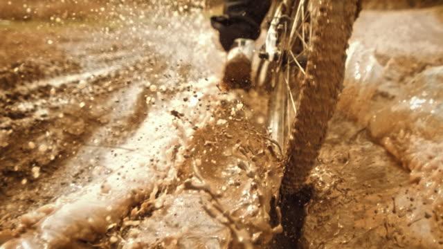 vídeos de stock, filmes e b-roll de super slow-mo: rastreamento motociclista equitação através da lama - câmera lenta