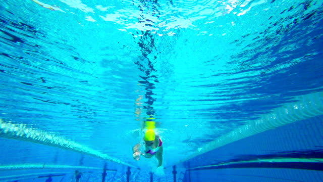 HD Super Slow-Mo Underwater: Young Woman Swimming Front Crawl