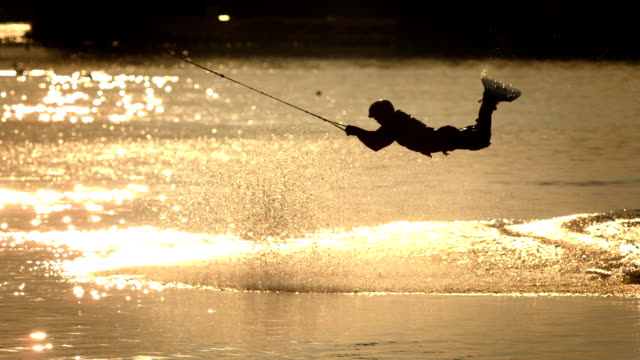 hd super slow-mo: wakeboarder jumping at sunset - waterskiing stock videos & royalty-free footage
