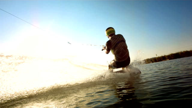 hd super slow-mo: wakeboarder jumping over the wake - wakeboarding stock videos and b-roll footage