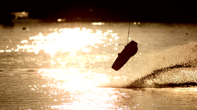 hd super slow-mo: wakeboarder performing jumping trick at sunset - wakeboarding stock videos and b-roll footage