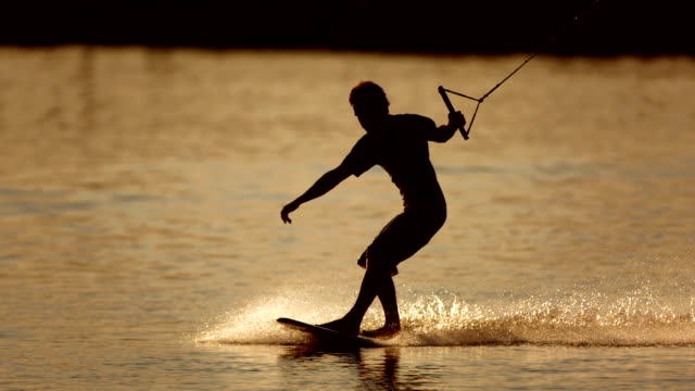 hd super slow-mo: wakeboarder sliding at sunset - wakeboarding stock videos and b-roll footage