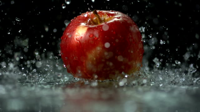 hd super slow-mo: water drops falling on apple - succulent stock videos & royalty-free footage