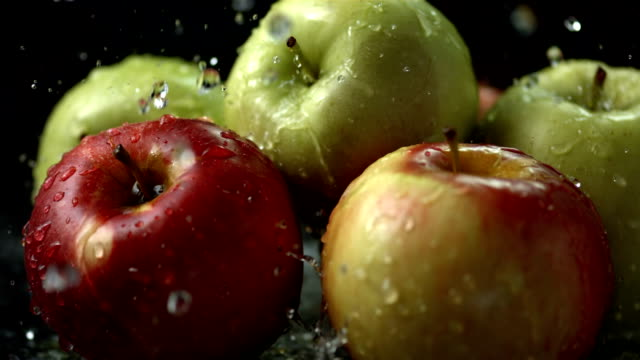 stockvideo's en b-roll-footage met hd super slow-mo: water drops falling on apples - sappig