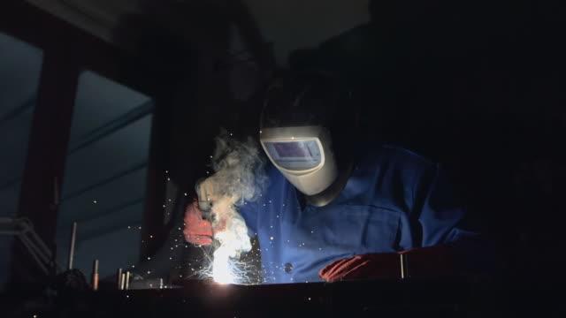 super slow-mo: schweißen in der werkstatt - arbeitssicherheit stock-videos und b-roll-filmmaterial