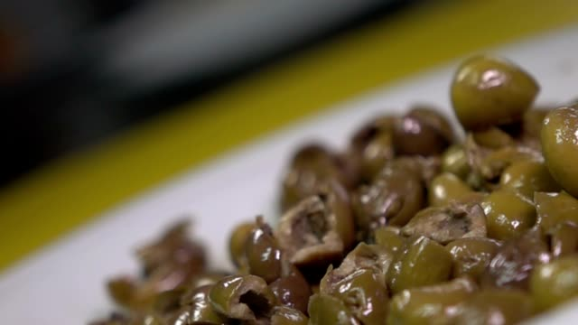 hd super slow-mo: wet olives falling on black glass - black olive stock videos & royalty-free footage