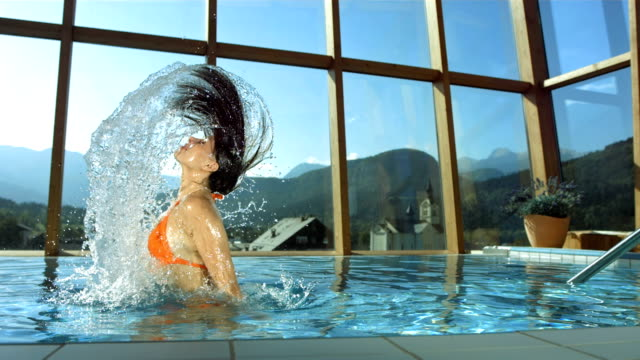 stockvideo's en b-roll-footage met hd super slow-mo: woman flipping hair in the pool - thermaalwater