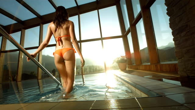 hd super slow-mo: woman getting into the pool at sunset - överflöd bildbanksvideor och videomaterial från bakom kulisserna