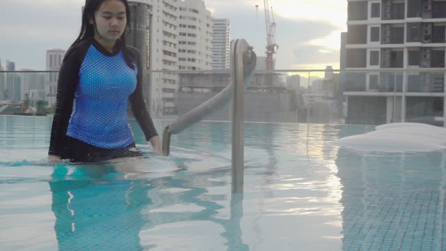 HD Super Slow-Mo: Woman Getting upon The Pool At Sunset.