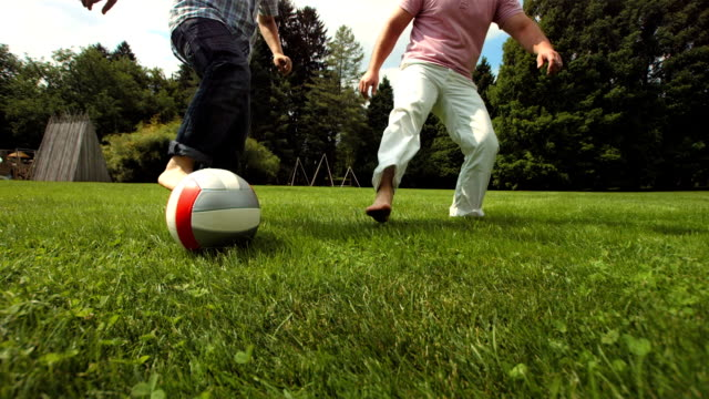 hd super slow-mo: young boy playing soccer with father - lawn stock videos & royalty-free footage