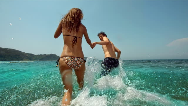 hd super slow-mo: young couple splashing into the sea - swimming stock videos & royalty-free footage