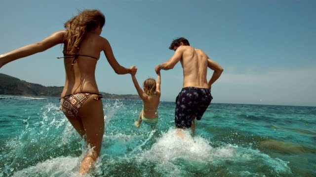 stockvideo's en b-roll-footage met hd super slow-mo: young family splashing into the sea - familie met één kind