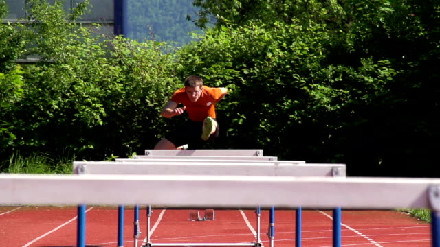 hd super slow-mo: young man at hurdle race 110m - obstacle course stock videos & royalty-free footage