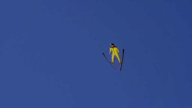 hd super slow-mo: young man performing ski jump landing - ski jumping stock videos and b-roll footage