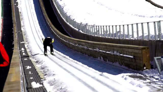 hd super slow-mo: young man performing ski jump - winter sport stock videos and b-roll footage