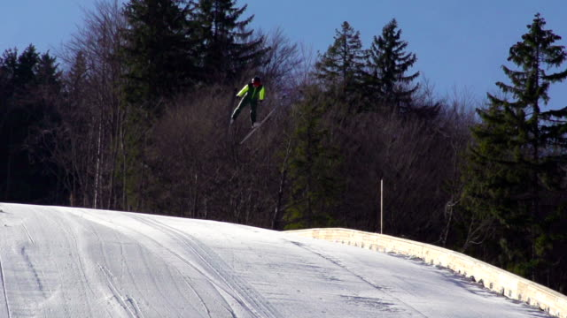hd super slow-mo: young man performing ski jump - ski jumping stock videos and b-roll footage