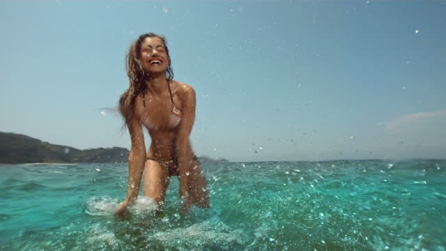 hd super slow-mo: young woman having fun splashing - beach bildbanksvideor och videomaterial från bakom kulisserna