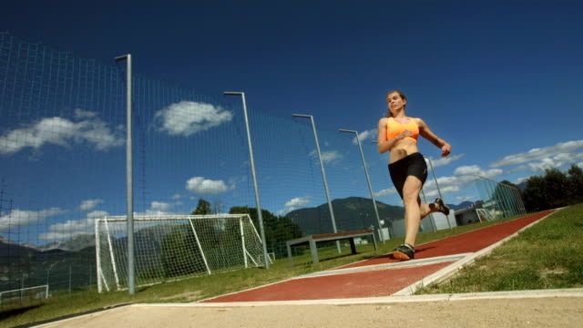 hd super slow-mo: young woman in a long jump - jump shot stock videos and b-roll footage