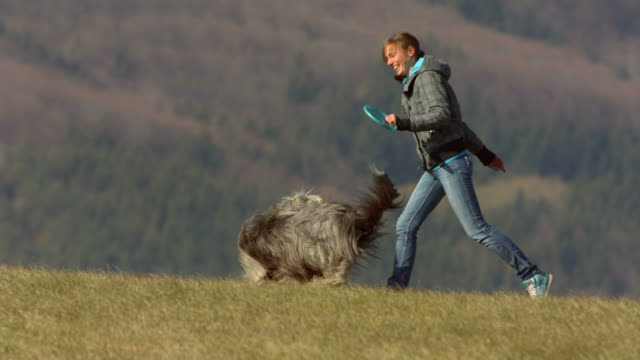 HD Super Slow-Mo: Young Woman Running With Her Dog