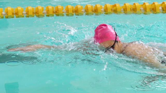 vídeos y material grabado en eventos de stock de hd super cámara lenta: joven mujer frente a nado estilo crol en la piscina - gorro de baño