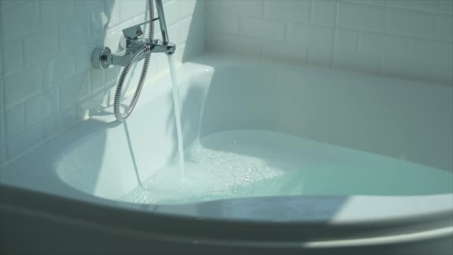 super slow-motion : running water splashing over bath tub - vasca da bagno video stock e b–roll