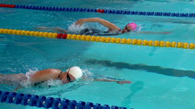 vídeos y material grabado en eventos de stock de hd super cámara lenta: dos mujeres jóvenes frente nado estilo crol en la piscina - gorro de baño