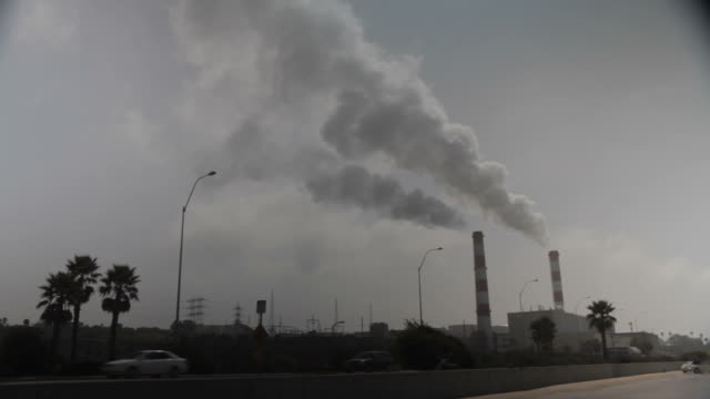 Super wide shot of chimneys pluming with smoke on the otherside of a busy freeway.