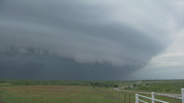 Supercell thunderstorm approaching from left of frame with gust front and shelf cloud.