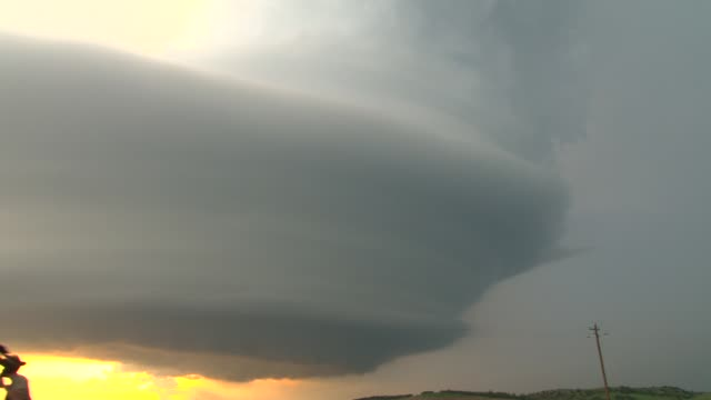 A supercell thunderstorm cloud hangs in the sky at dusk