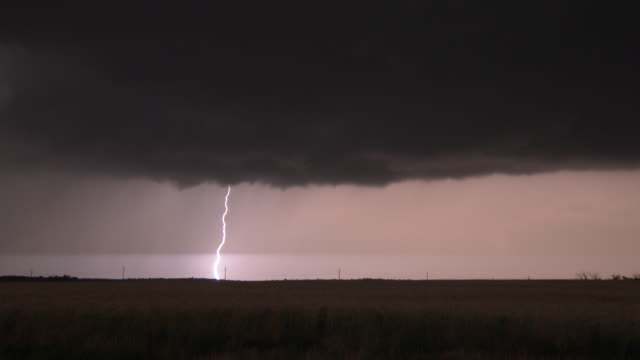 a supercell thunderstorm over rural texas farmland produces vivid cloud to ground lightning bolts striking dangerously close to the cameraman during... - lightning strike stock videos and b-roll footage