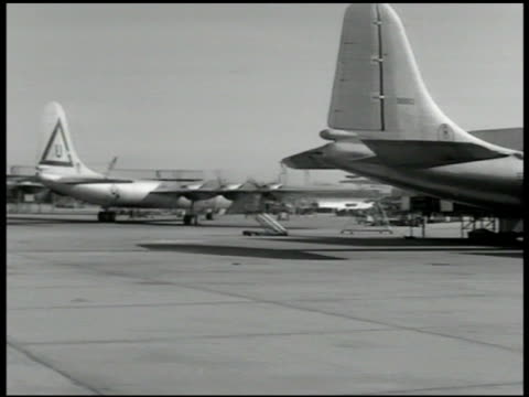 B29 'Superfortress' bombers docked in airport WS B29 'Superfortress' bomber taxiing on tarmac USAF General Curtis LeMay w/ other officers looking at...