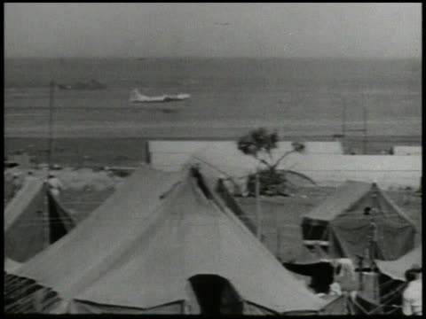 superfortress coming in for emergency landing crash landing into water soldiers watching from military base lower fg ws downed b29 floating in water... - schlacht um iwojima stock-videos und b-roll-filmmaterial