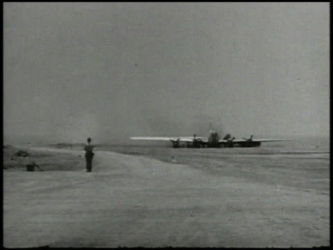 superfortress coming in for emergency landing, crash landing on runway, explosion, fire, soldiers putting out fire, rescuing crew member w/ burn... - 空爆点の映像素材/bロール