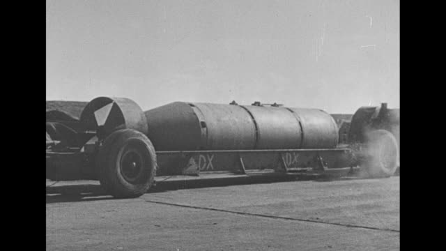 superfortress flying overhead / large bomb being hauled along at airfield past smaller bomb / b-29s lined up on runway with propellers spinning ready... - b29 stock videos & royalty-free footage