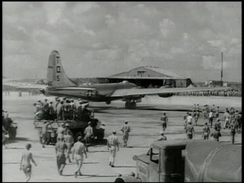Superfortress taxiing on military airbase people gathering around XXI BC members deplaning greeting other soldiers male talking about arrival WWII...