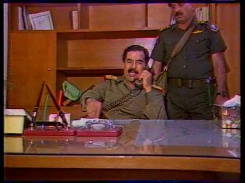 baghdad cms iraqi pres saddam hussein on phone at desk as officer standing in b/g zoom in itn r 23.7.88 tx 20.7.91/20.45 - saddam hussein stock videos & royalty-free footage
