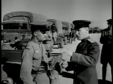 vídeos de stock, filmes e b-roll de superimposed over russian officer and truck drivers. russian ussr soldier talking w/ soviet officer truck convoy bg. drivers getting into trucks... - 1946